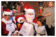 santa and mrs claus handing gift bag to boy