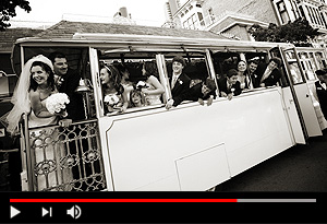 video screen showing white wedding trolley and wedding party looking out the windows