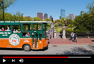 video screen showing old town trolley tour in Boston driving past public garden