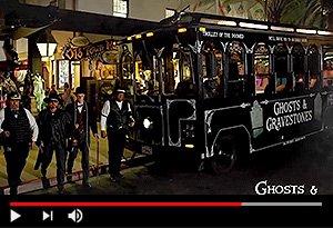 video screen showing san diego ghost hosts next to haunted trolley at night