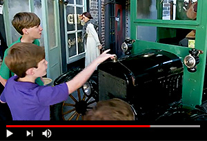 video screen showing kids pointing at antique car