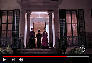 video screen showing ghost hosts standing on the entrance steps to andrew low house at night