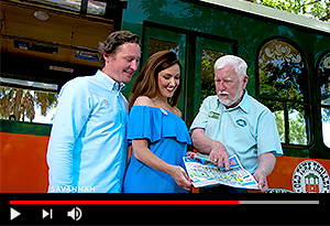 video screen showing guests and trolley conductor point to a map with trolley in the background