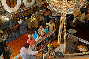 aerial view Key West Shipwreck Treasure Museum interior showing a tour guide showings guests variuos treasures