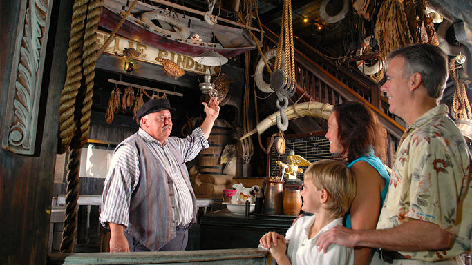Aerial view of the Key West Shipwreck Treasure Museum interior showing a tour guide showcasing various treasures to guests