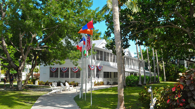 Truman Little White House exterior picture featuring a white house with flag bunting, trees and various flags on poles