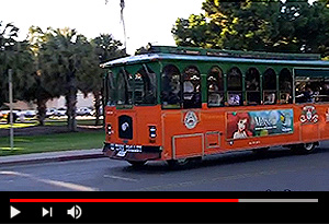 video screen showing san diego trolley and trees in background