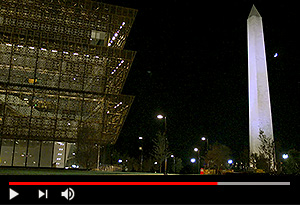 video screen showing african american museum and washington monument glowing at night