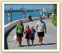 picture of family made of woman, man and two children walking next to the water in San Diego